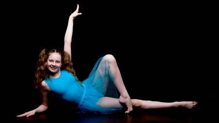 Meisjesturner in de studio op een zwarte achtergrond voert gymnas uit Stockfoto