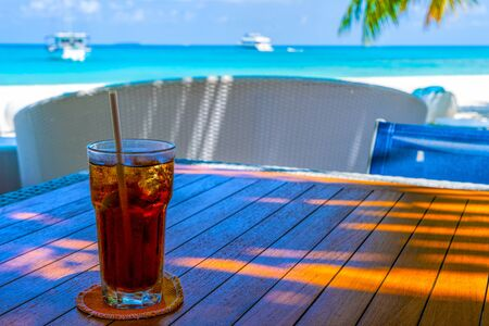 A glass of cold cocktail on a table on the beach in a restaurant 版權商用圖片