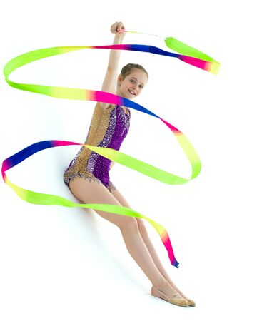 Girl gymnast performs exercises with tape. Фото со стока