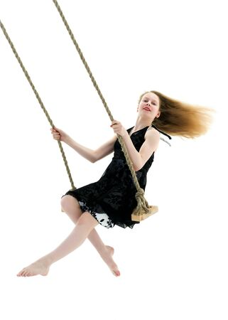 Beautiful teen school girl swinging on a swing. Concept summer v