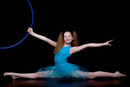 Girl gymnast in the studio on a black background performs gymnas Banco de Imagens