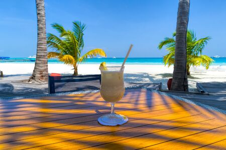 A glass of cold cocktail on a table on the beach in a restaurant Standard-Bild - 140181541