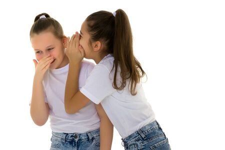 Two cheerful little girls share secrets in each other s ear. Banco de Imagens
