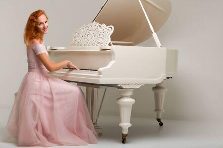 Beautiful young woman near a white grand piano.