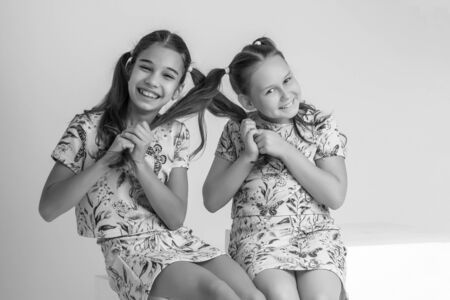 Little girls pull each others pigtails.