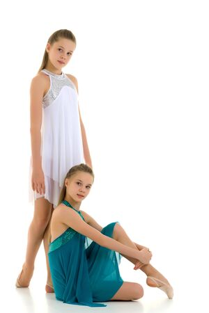 Two Teenage Girls in Sport Dresses Posing Together on White. Фото со стока