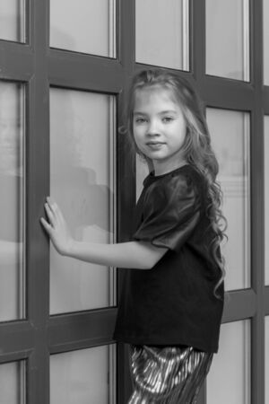 Little girl posing in studio near a large panoramic window Banque d'images