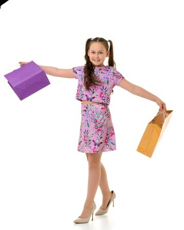 Cheerful little girl in large shoes taken from her mother. Archivio Fotografico