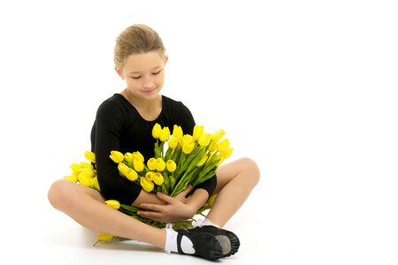 Beautiful little girl gymnast with a bouquet of flowers in the studio. The concept of sports victory.