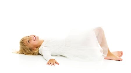 Little girl lies on the floor.Studio photo shoot on a white back