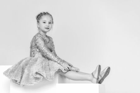 Cute little girl is sitting in the studio on the white stairs. style and fashion concept, happy childhood.