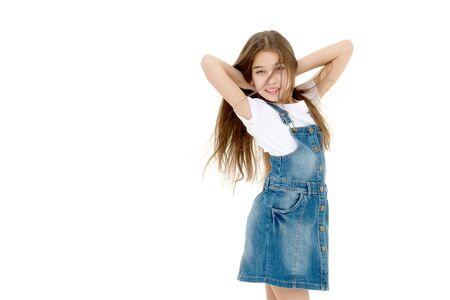 A little girl fixes her hair.