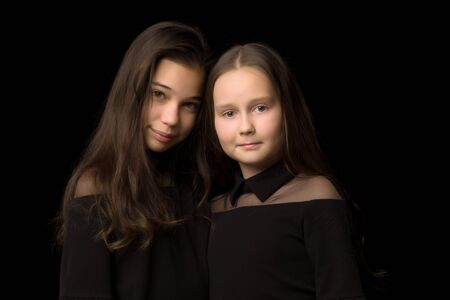 Two little girls posing in the studio on a black background. Sty