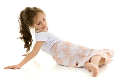 Beautiful Preteen Girl Lying on the Floor Against White Background