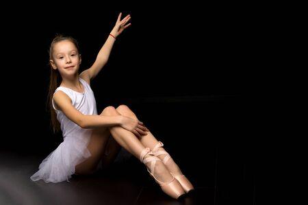 Beautiful little ballerina on a black background. dance concept.