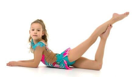 Charming little girl doing gymnastic exercises in the studio on a white background