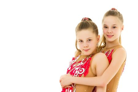 Pretty Girls Gymnasts Performing Rhythmic Gymnastics Exercise. Stock Photo