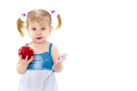 Little girl with apple. Isolated on white background. Фото со стока