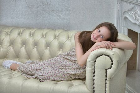 Beautiful young girl sitting on the sofa by the fireplace.