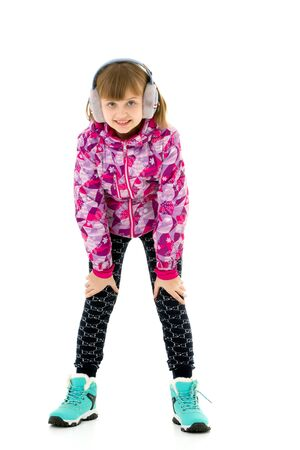 A little girl with headphones listening to music.