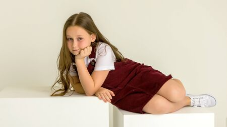 Little girl poses for a magazine in the studio on a white cube. Stok Fotoğraf
