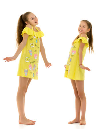 Side View of Barefoot Girls Looking at Each Other Standing on One Leg
