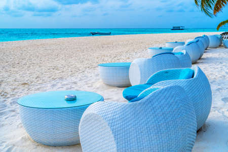 Beach chairs on the white sand on the shore of a beautiful tropical sea.