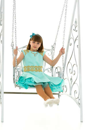 Beautiful teen school girl swinging on a swing. Concept summer vacation.