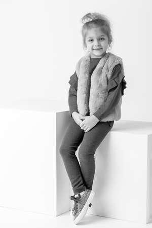 Full Length Portrait of Smiling Girl Sitting with her Feet Dangl