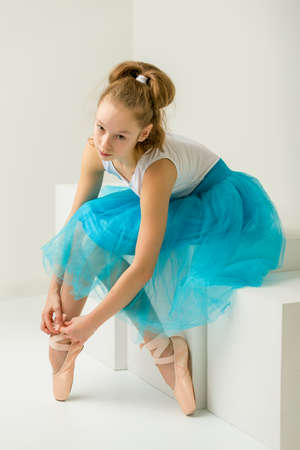 Girl ballerina puts on pointe shoes. The concept of dancing. Banque d'images