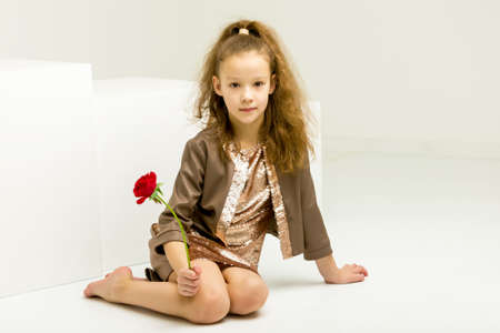 Beautiful girl sitting with her head bowed to the side with a rose flower