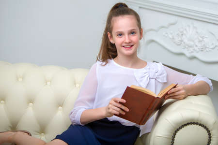 An adorable little girl sits on a sofa and reads a book enthusiastically.