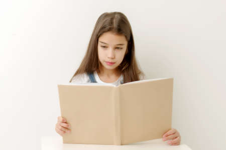 Little girl with a book. Isolated over white background