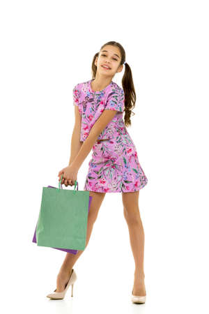 Cheerful little girl in mother's high-heeled shoes of large size. The girl presents herself as an adult lady. Isolated on a white background. Archivio Fotografico
