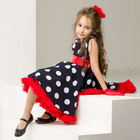 Beautiful Girl Wearing Polka Dot Dress and Black Shoes Sitting on White Stairs and Smiling at Camera, Full Length Portrait of Charming Coquettish Girl Posing in Retro Fashion Dress in Studio