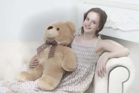 Beautiful teenage girl of school age sitting on a sofa with a teddy bear.