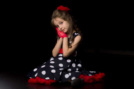 Girl dressed in retro fashion clothes sitting on a black background.