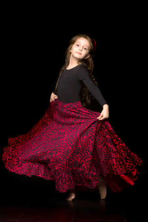 Girl Dancer in Black and Red Dress Performing on Black Background.