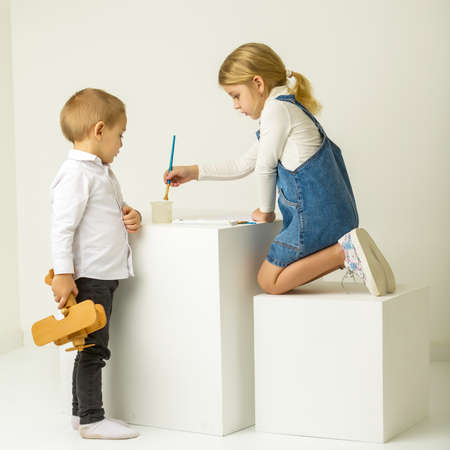 Cute Girl Sitting on Her Knees and Painting, Brother Looking at Her.