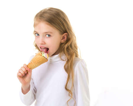 Little girl gently licks a very cold ice cream.