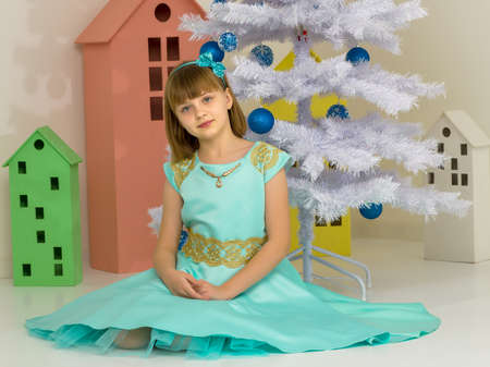 Girl in Stylish Dress Sitting on the Floor in Front of Christmas Tree.
