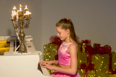 Portrait of Beautiful Smiling Girl Sitting at Piano Looking at Camera.