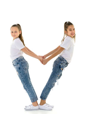 Two little girls hold hands, on a black background.