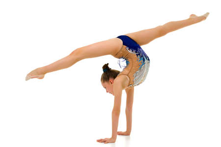 Beautiful girl gymnast performs a handstand.