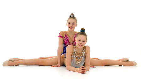 Girls gymnasts perform exercises on twine. 写真素材