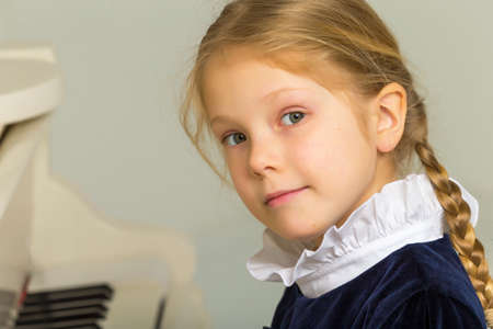Beautiful Blonde Little Girl Playing Piano and Looking at Camera