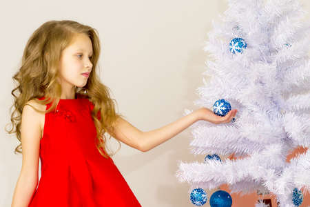 Girl Posing Next to White Christmas Tree Holding Blue Bauble.