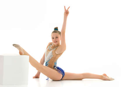 Beautiful girl gymnast on a white cube does an acrobatic twine element. Banque d'images