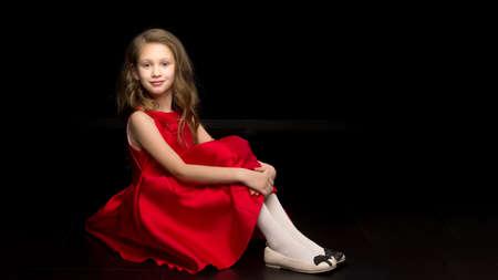 of Lovely Preteen Girl Sitting on the Floor Hugging Her Knees