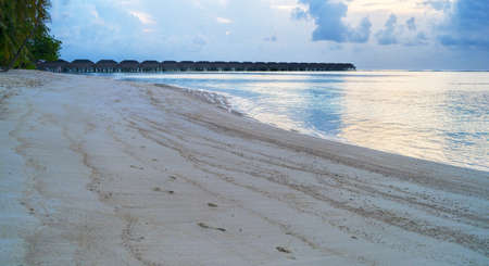 Wooden bridges leading to the huts on the shores of the tropical, warm sea. Maldives. Tourism concept.